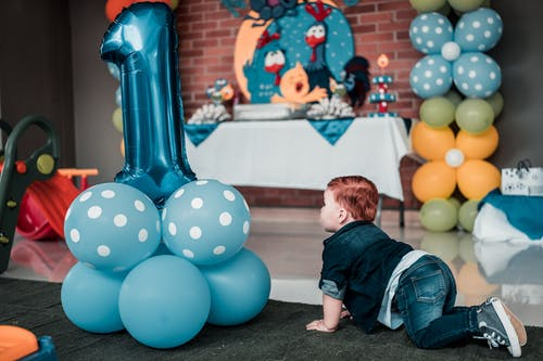 Baby in Blue Denim Jacket Crawling on Floor Near the Balloons