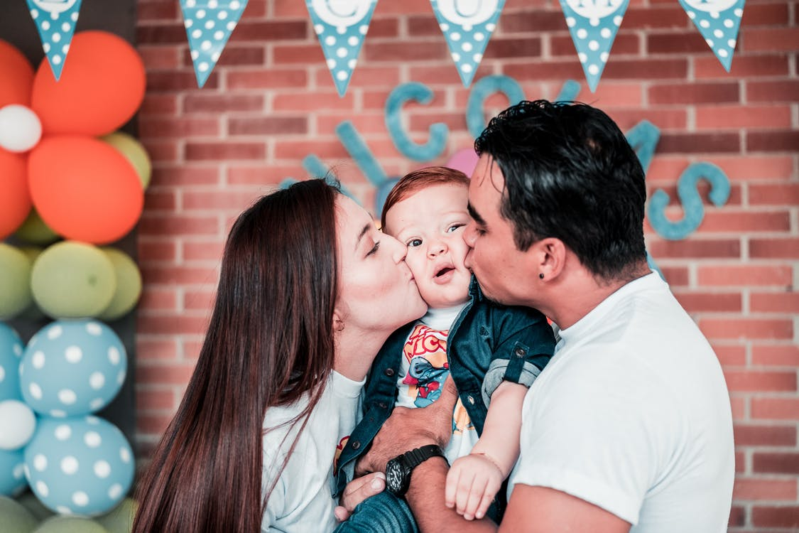 Photo of Man and Woman Kissing Their Baby