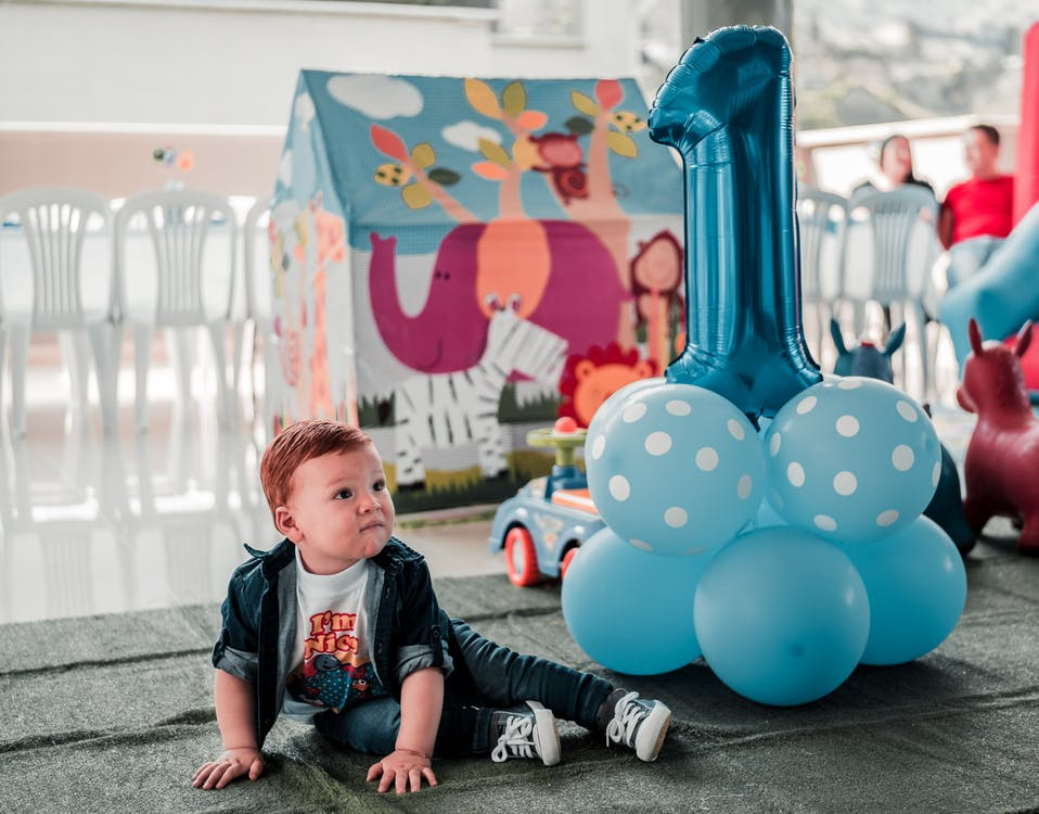 Boy Sitting on Floor With Balloons