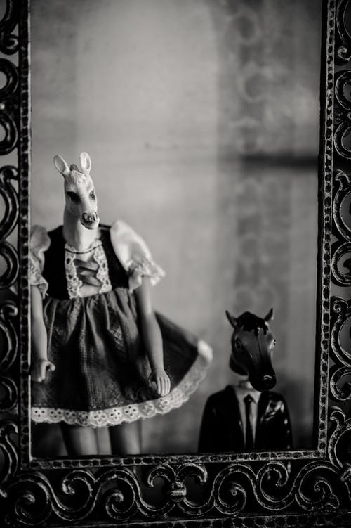 Grayscale Photo of Woman in Black Dress Wearing A Mask Of An Animal Head