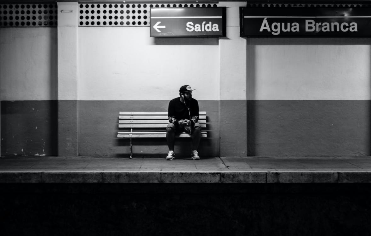 Man Sitting on Bench in Train Station
