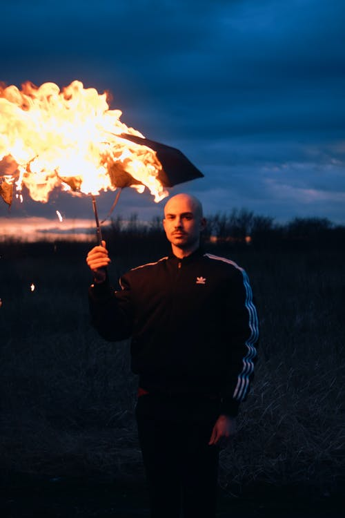 Man in Black and White Jacket Holding Fire