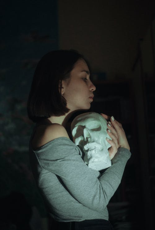 Side View Photo of Woman in Gray Tank Top Holding White Skull