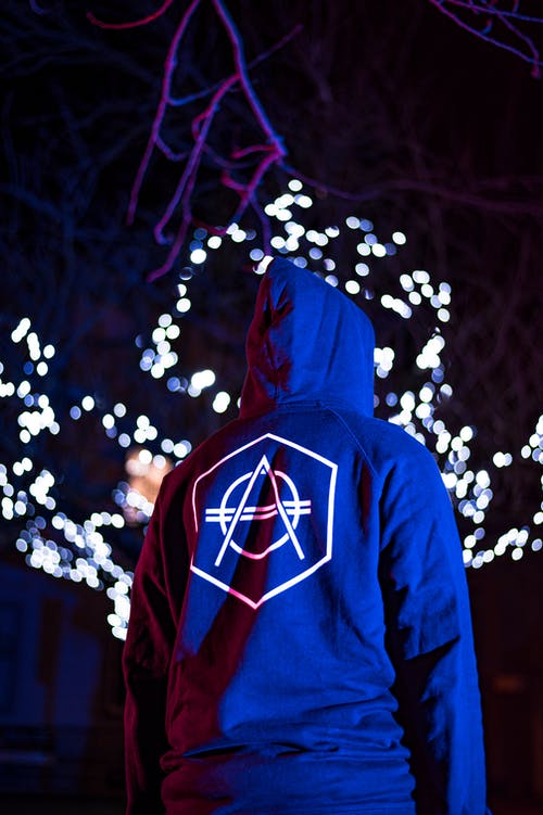 Person in Red and Blue Hoodie Standing in Front of White String Lights