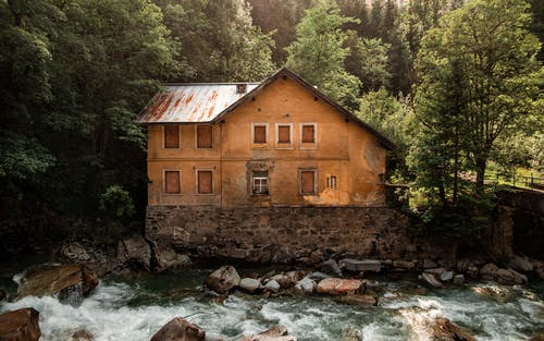 Photo Of Brown House In Front Of River During Daytime
