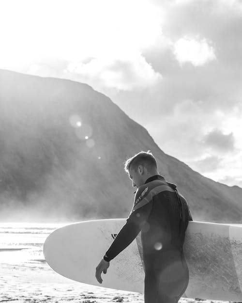 Monochrome Photo of Man Holding Surfboard