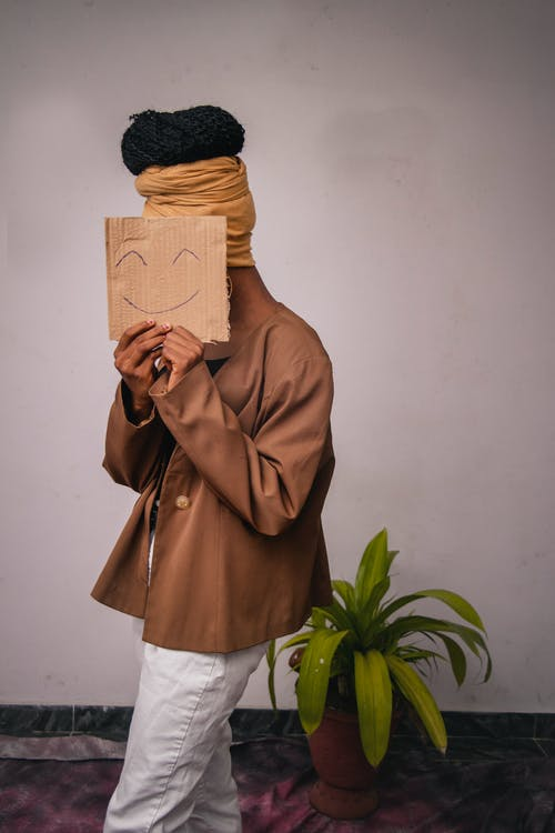Photography of A Woman Holding A Cardboard With Emoticon