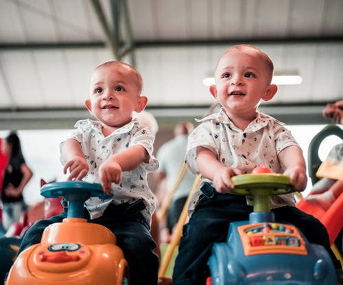 Photo of Two Babies Sitting on Toy Cars