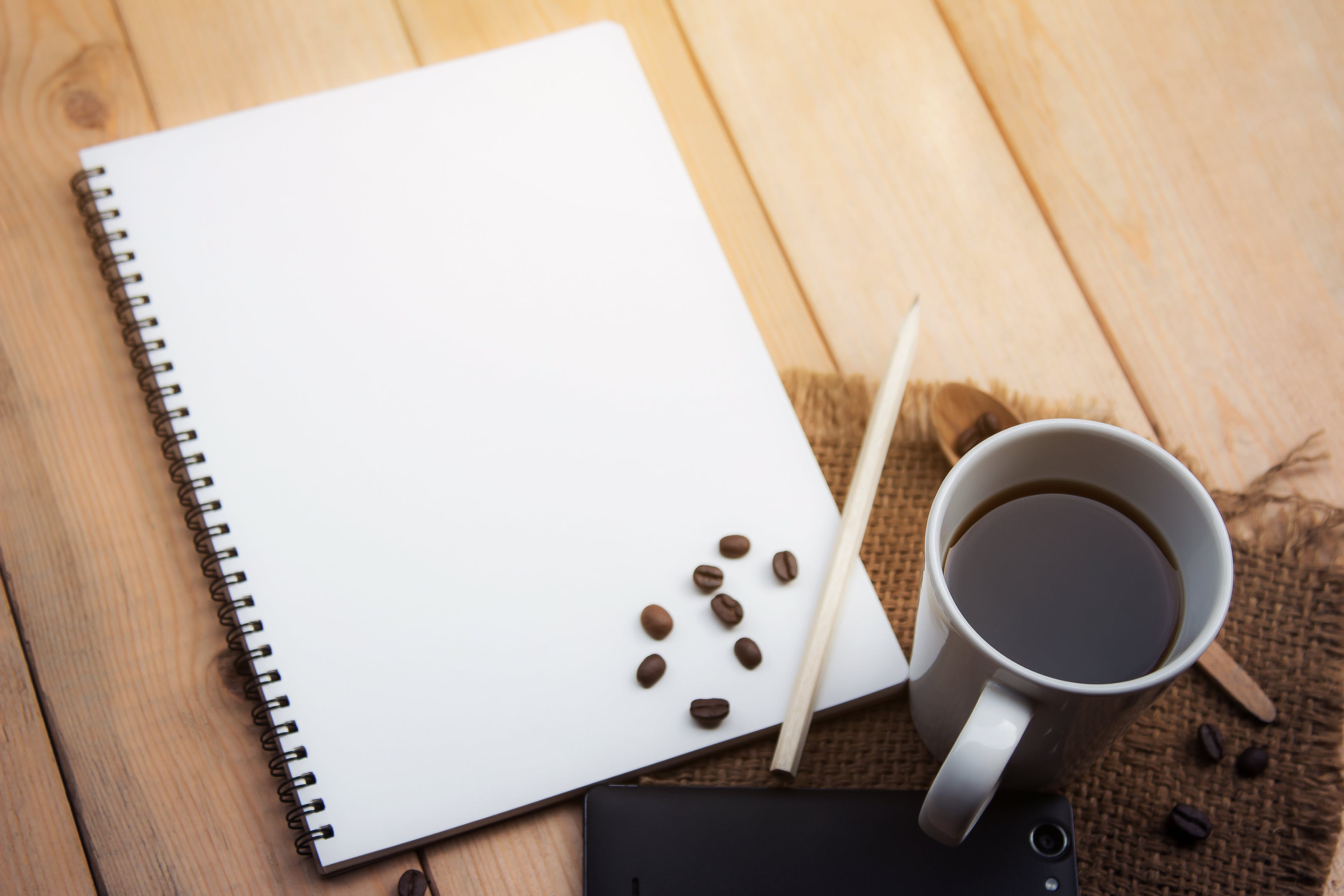 White Sketch Pad Beside Cup of Coffee