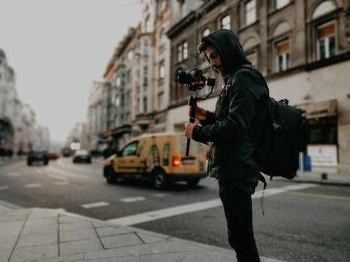 Photo Of Man Holding Black Camera On Side Of The Street