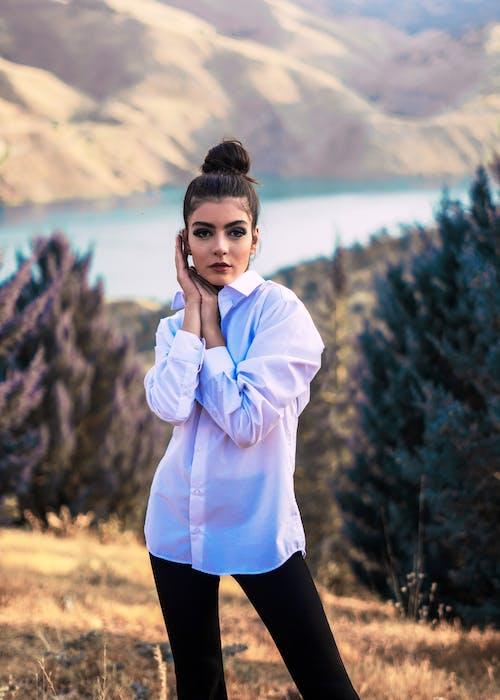 Stylish woman standing in mountainous terrain