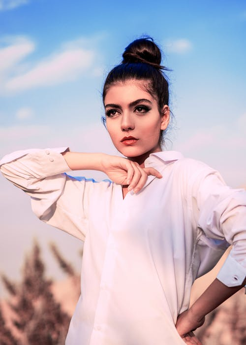 Cool young woman in white shirt and with dark makeup standing with hand on waist and looking away