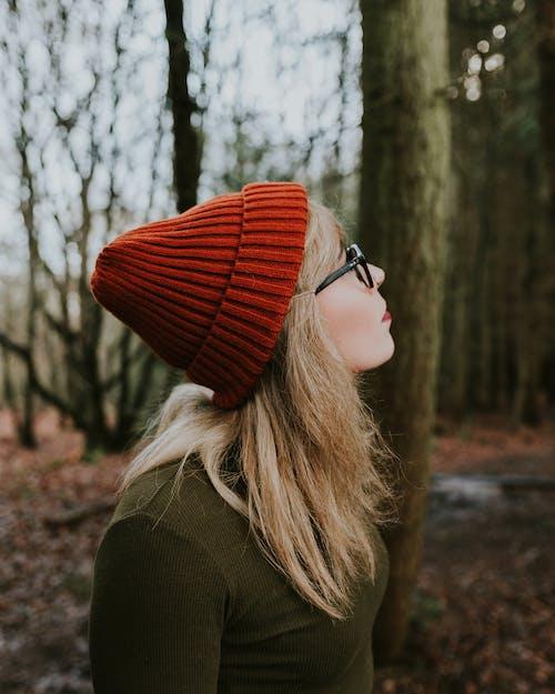 Женщина в красной вязаной шапке и коричневом свитере