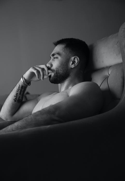 Topless Man Sitting on Couch