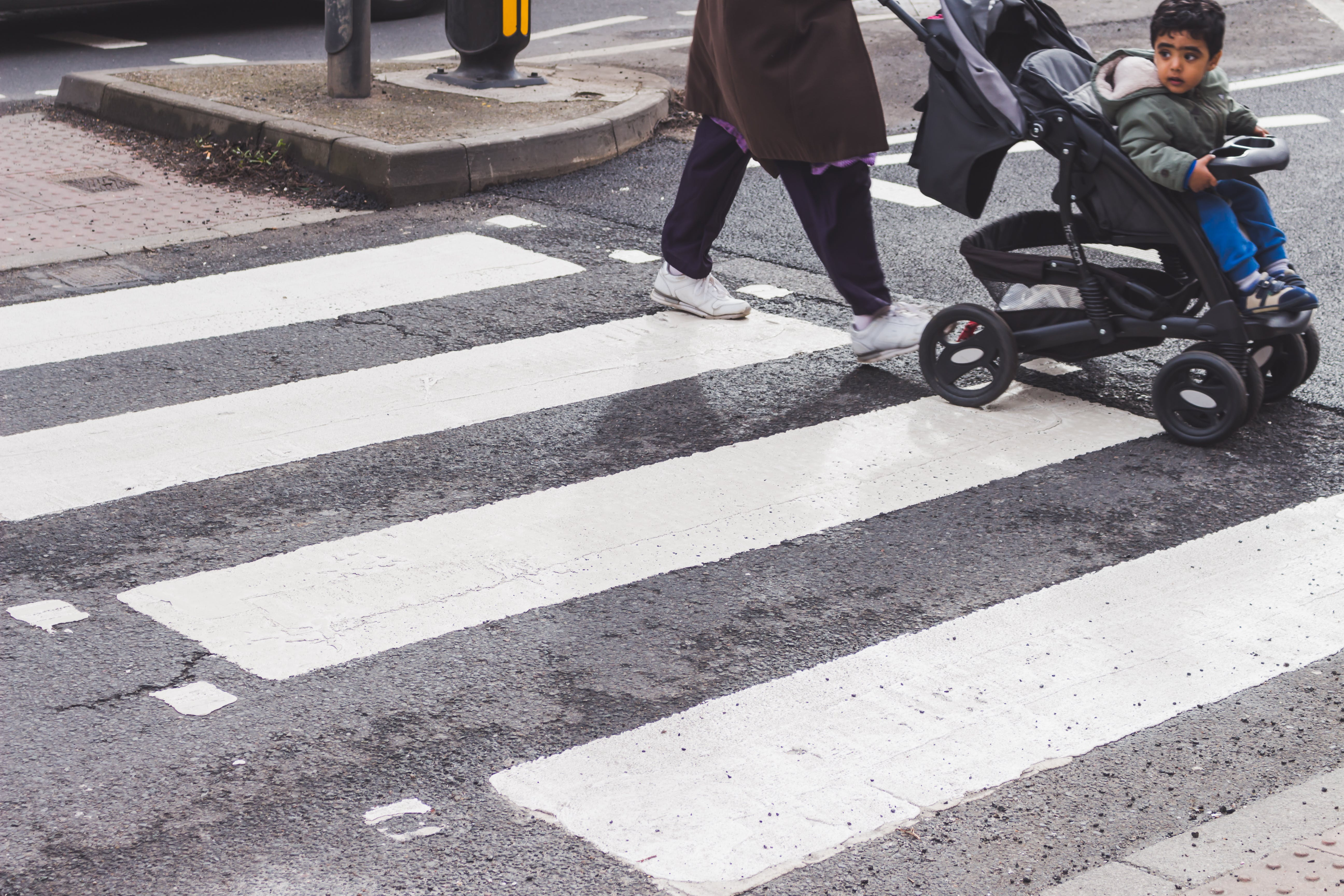 Person Pushing Stroller Crosswalk on Pedestrian Lane