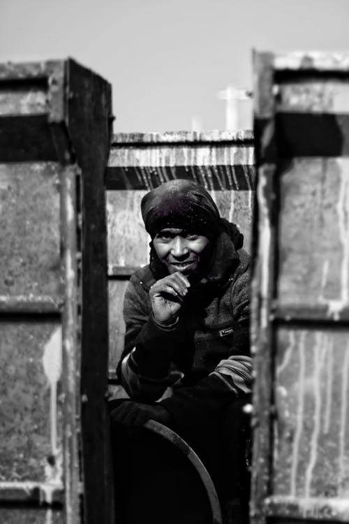 Black and white of ethnic male worker in warm clothes during working day in factory