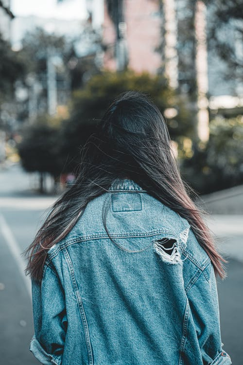 Back View Photo of Woman Wearing Denim Jacket