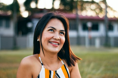 Delighted young Asian lady smiling while chilling on grassy meadow during summer holidays