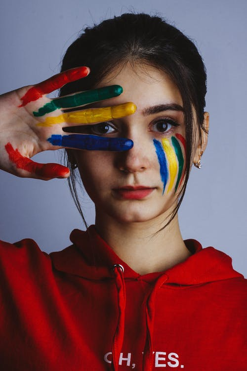 Woman in Red Hoodie Jacket With Blue Yellow and Green Paint on Face