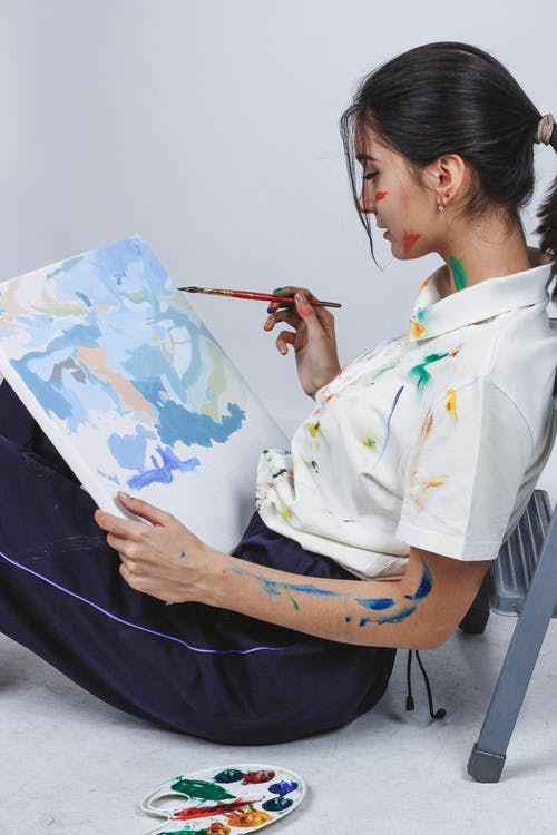 Side View Photo of Woman Sitting on the Ground Painting Canvas