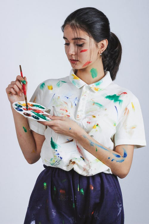 Photo of Standing Woman Covered in Paint Holding Color Palette and Paint Brush Posing While Looking Down