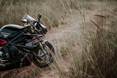 Photo of Black and Red Triumph Daytona Motorcycle Parked  on Brown Grass Field