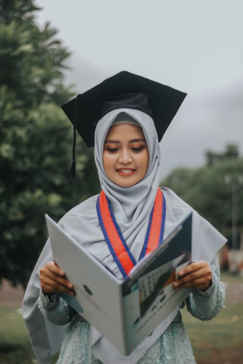 Woman in White Academic Dress Holding Book