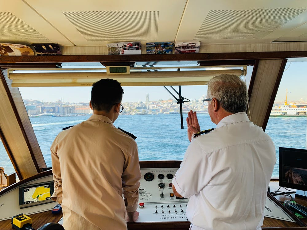 A captain is instructing the other person on the ship. | Photo: Pexels