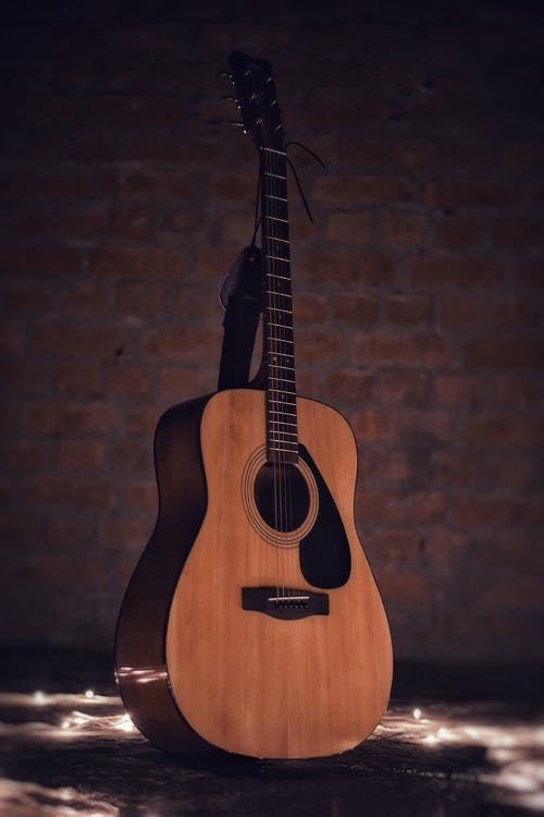 Acoustic Guitar on Brown Brick Wall