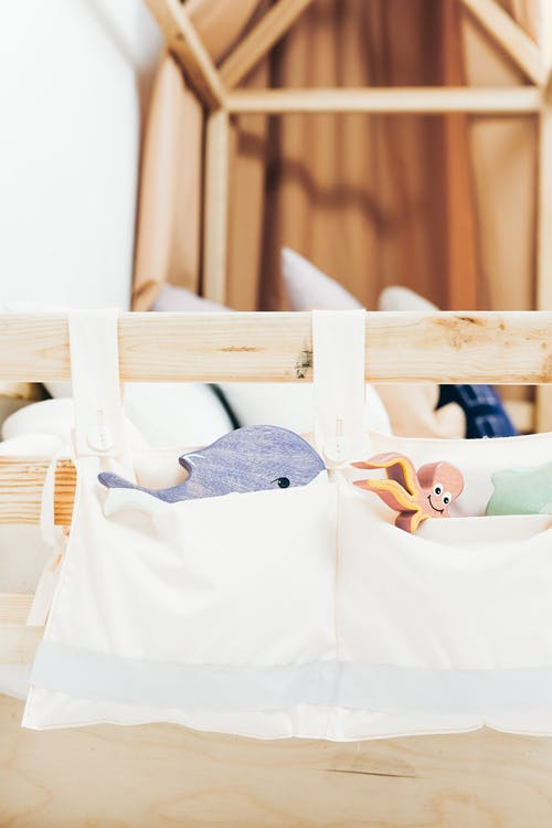 White Cloth Bag on Brown Wooden Bed