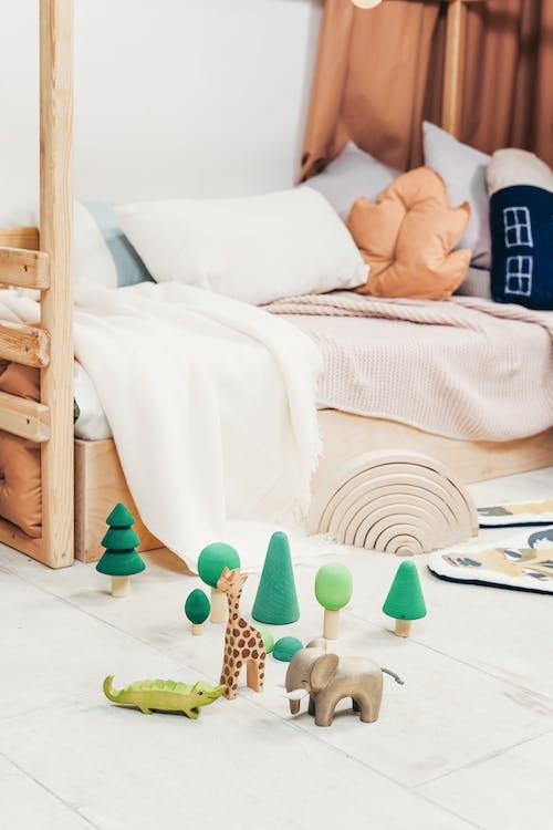 白いベッドリネンと茶色の木製ベッドフレーム