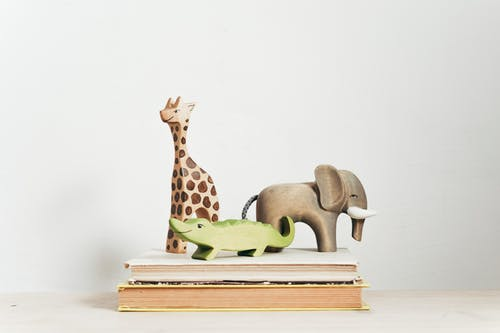 Brown and Green Giraffe Figurine on Book