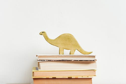 Brown Wooden Dinosaur Figurine on White Book