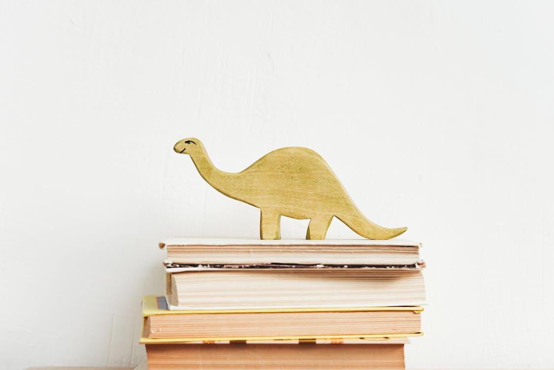 Brown Wooden Dinosaur Figurine on White Book