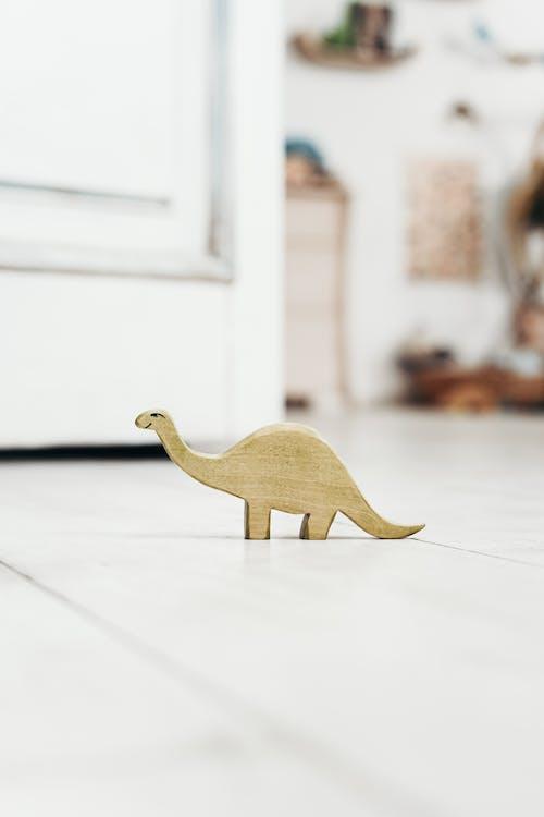 Brown Wooden Dinosaur Figurine on White Floor