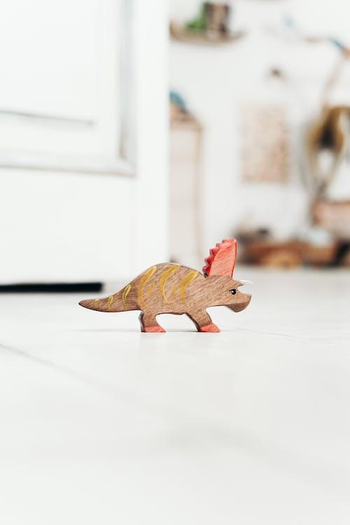 Brown Dinosaur Toy on White Floor