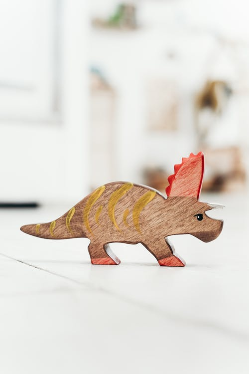 Brown and Red Dinosaur Figurine on the Floor