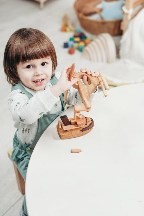 Child in White Long Sleeve Top Playing With Brown Wooden Toys