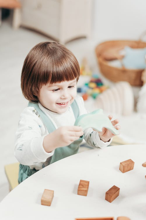 Child in White Long Sleeve Top Playing with Toys