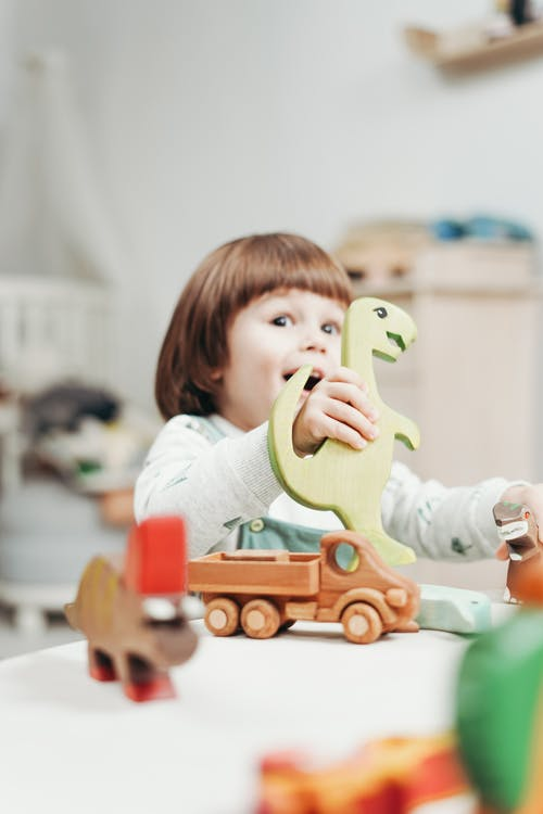 Girl in White Long Sleeve Top Playing With Toys