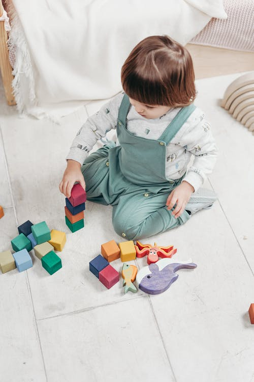 A Child Sitting on The Floor Playing With Toys