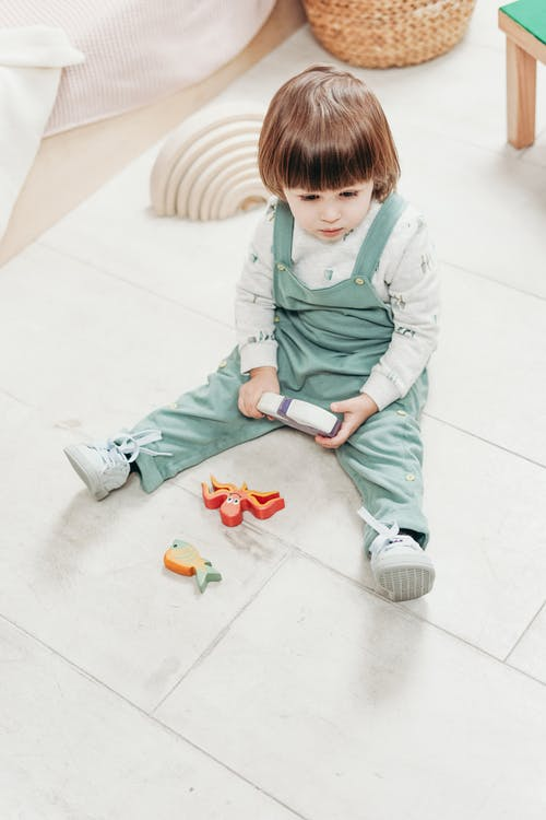 A Child Sitting On The Floor With Toys