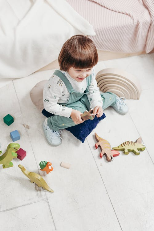Girl in White Long Sleeve Top and Dungaree Trousers Sitting on White Floor Tiles Playing with Toys