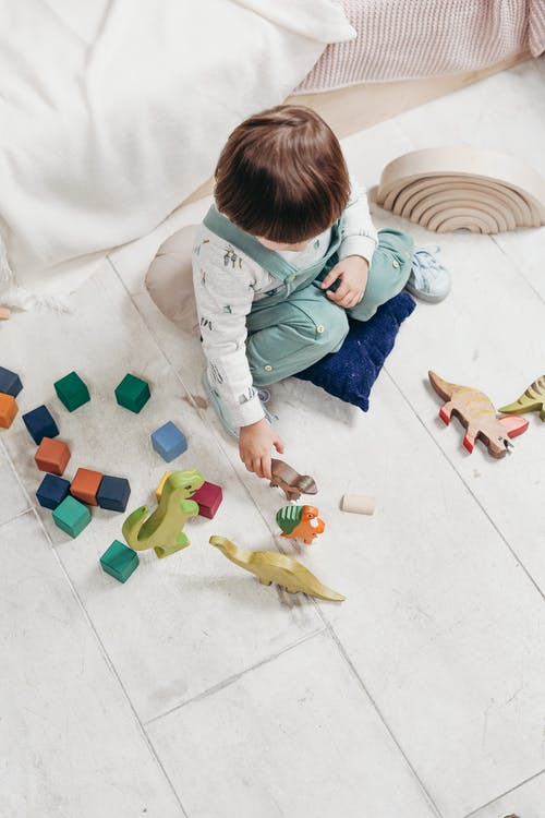 Child in White Long Sleeve Top and Dungaree Trousers Playing With Colorful Lego Blocks