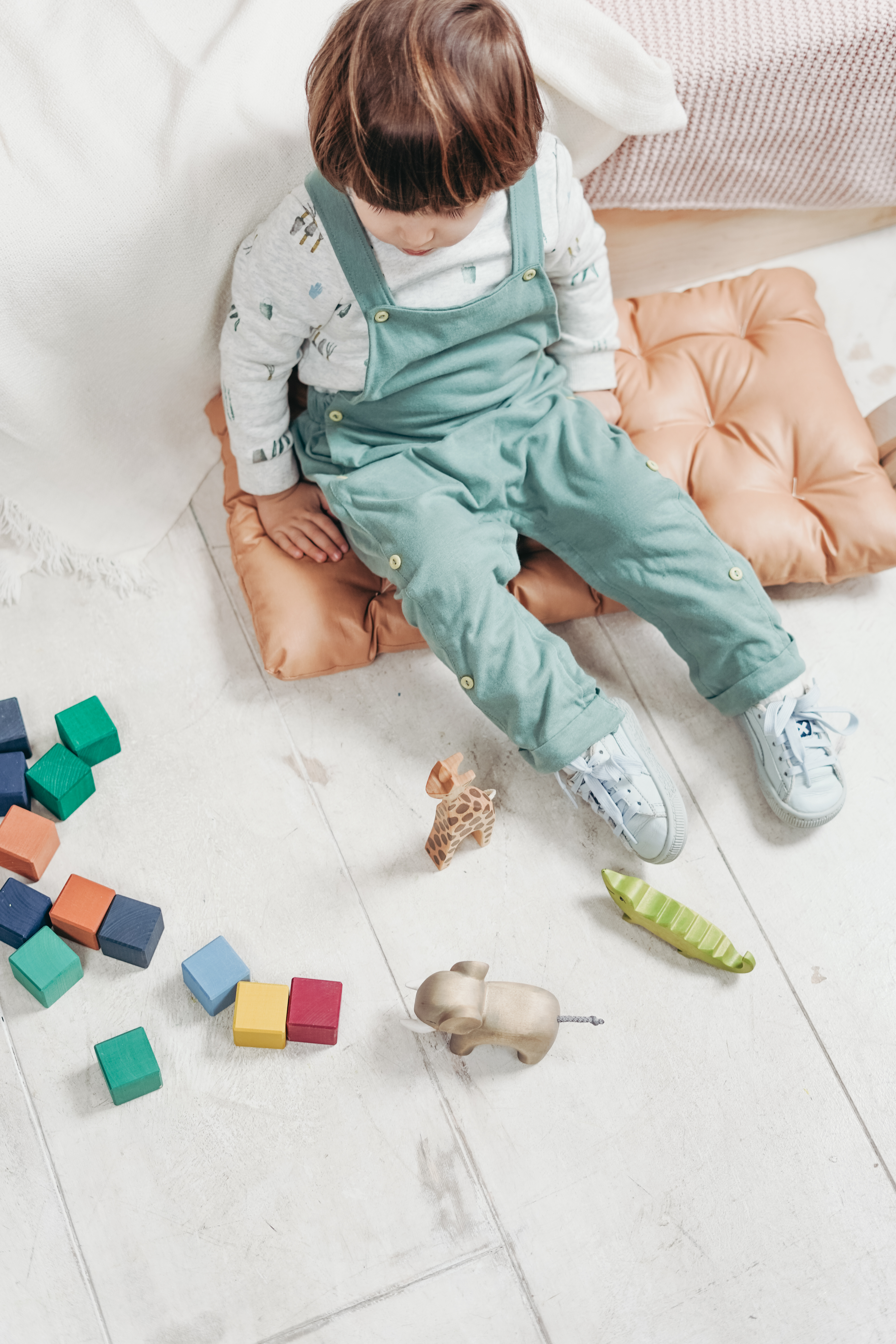 child in green over all sitting on a pillow