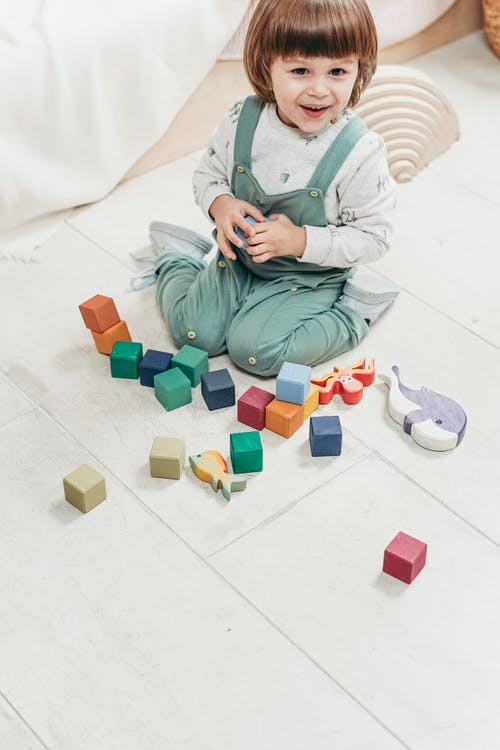 Child in White Long-sleeve Top and Teal Dungaree Trousers Playing With Lego Blocks
