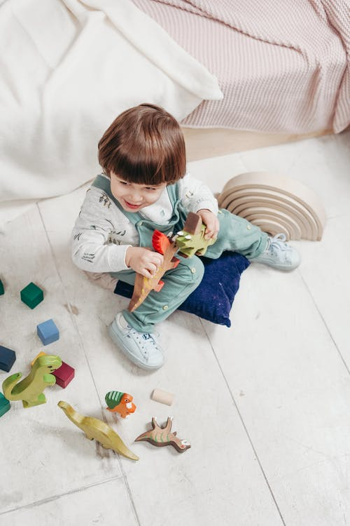 Child in White Long-sleeve Top and Teal Dungaree Trousers Playing With Toys