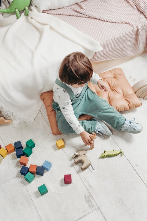 Child in White Long-sleeve Top and Dungaree Trousers Playing With Toys