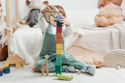 Child in Green and White Long Sleeve Top and Dungaree Trousers Holding Blue and Yellow Lego Blocks