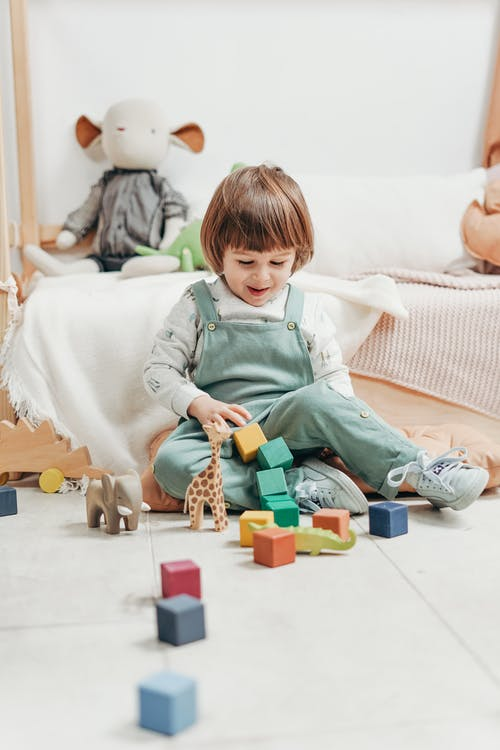 Boy in White Long Sleeve Top and Dungaree Trousers Playing Lego Blocks